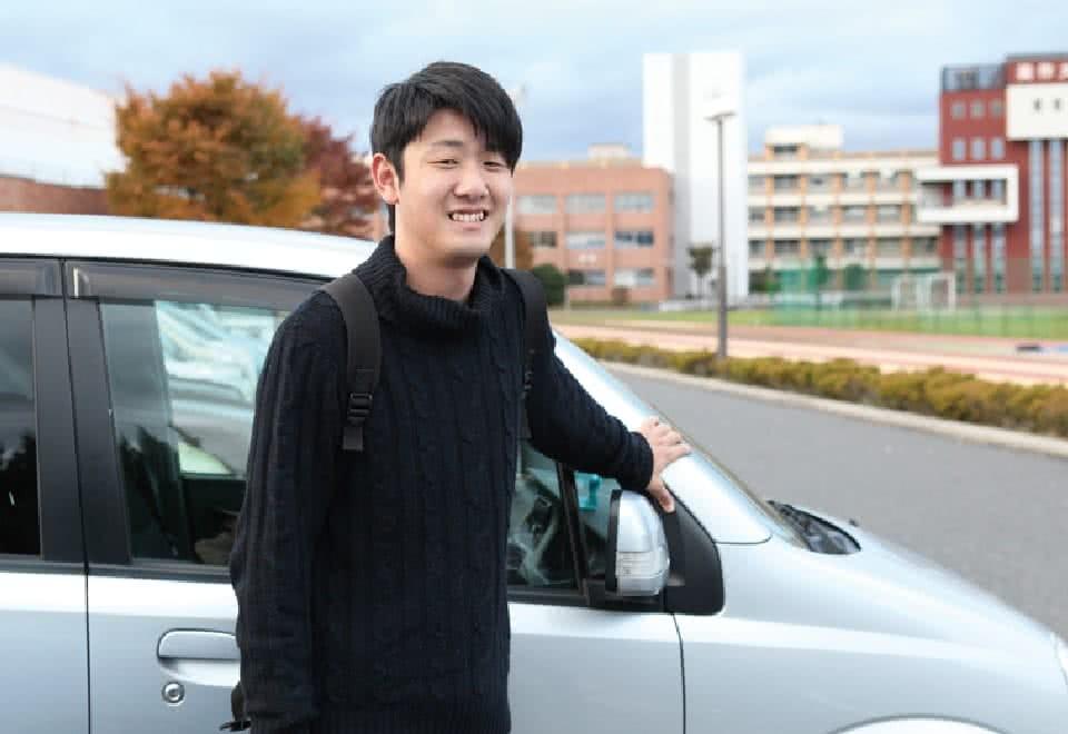 写真:自家用車の前に立つCさん