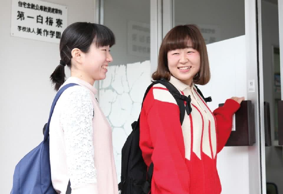 写真:学生寮の扉を開けて中に入ろうとするDさんと友達