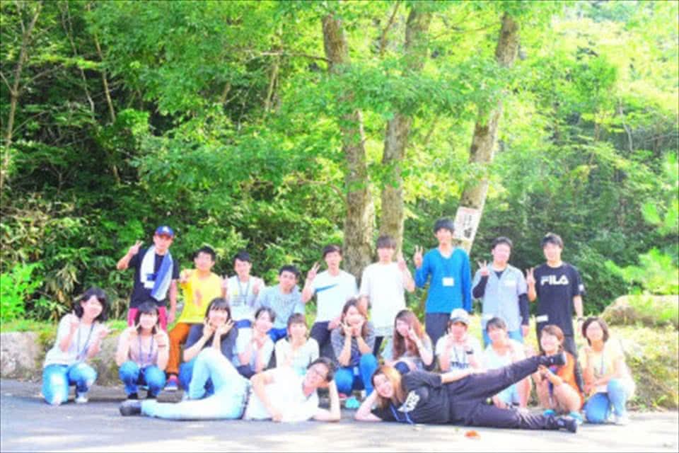 写真:緑生い茂る森林を背景に里親・里子支援サークルのメンバーが並んでいる様子