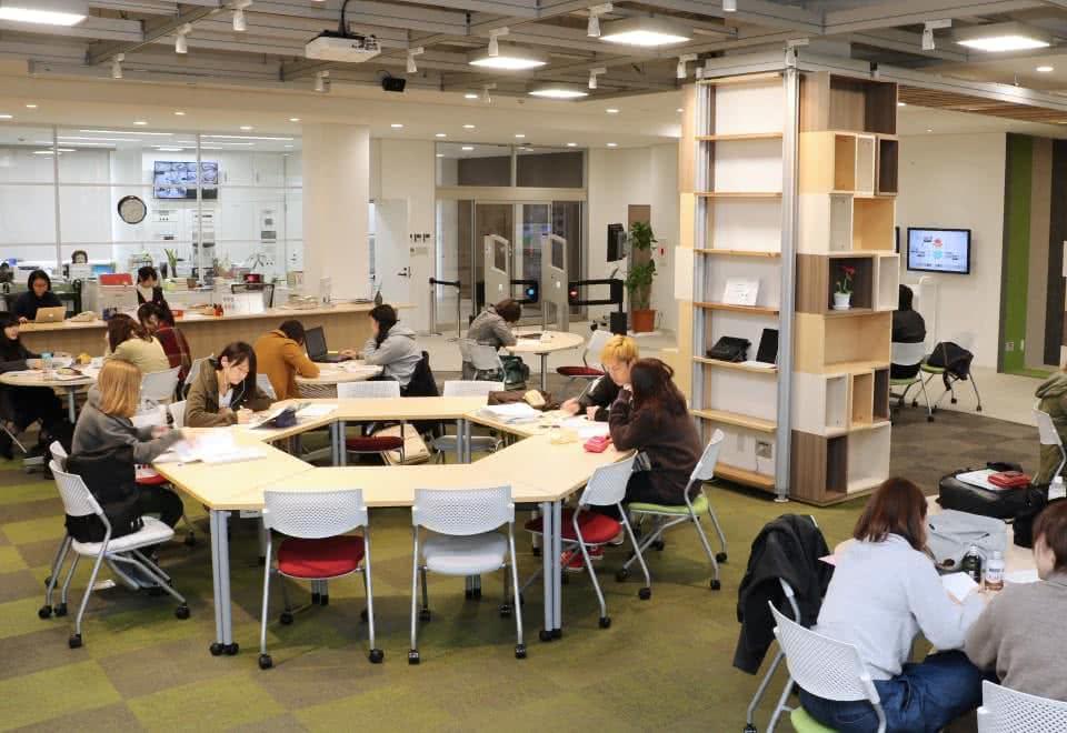 写真:ラーニング・コモンズの机で勉強をしている学生たち・机は六角形に組み合わされている。