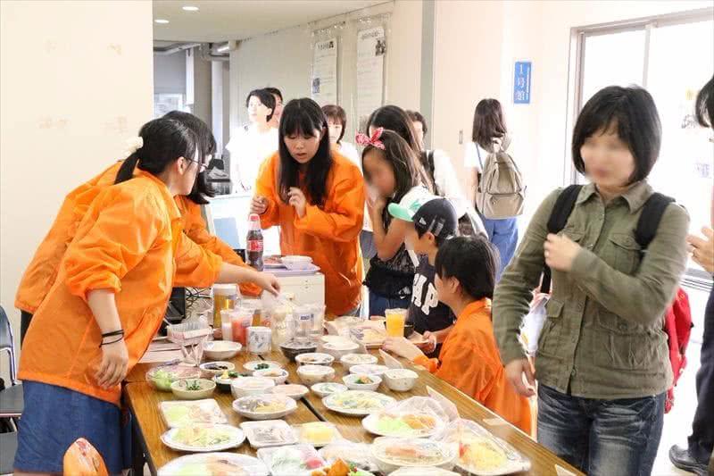 写真:並べられた料理とそれを見る人たち