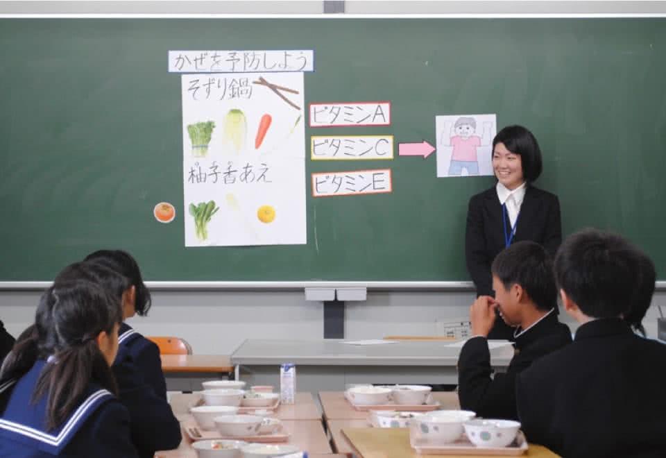 写真:小学校・中学校の黒板に自作の教材を貼って、給食時間の指導を行っている様子