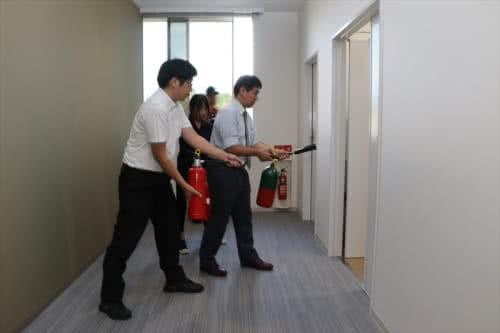 写真:消火器を使って火元を消化する職員