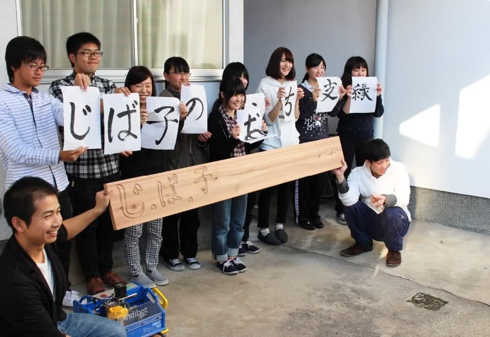 写真:じ・ば・子のおうち支縁オープニングセレモニーにて、看板を持って記念撮影する学生と関係者