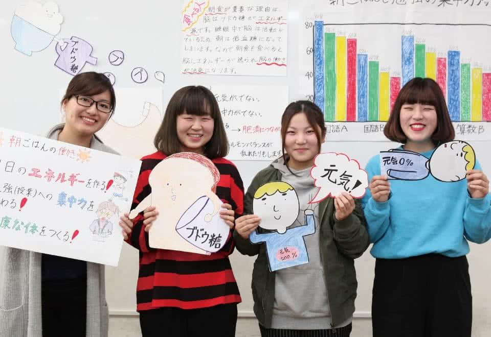 写真:女性が4名手作りの資料を持ち3分間スピーチの練習をしている様子