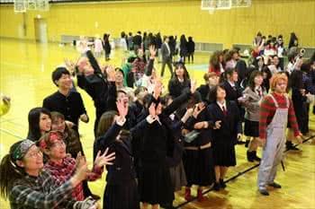 写真:お菓子投げでお菓子をつかもうとする大勢の学生