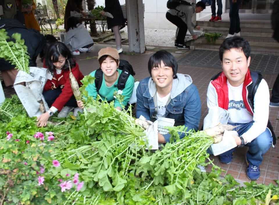 写真:無料野菜市場で並べられた野菜とそれを手に持つ学生たち