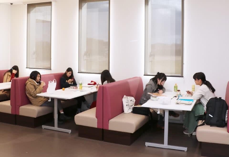 写真:オープンコモンズのダイナーテーブルでグループごとに向かい合わせに座る学生たち。勉強や休憩など思い思いに過ごしている。