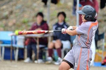 写真:バットでボールをとらえる選手