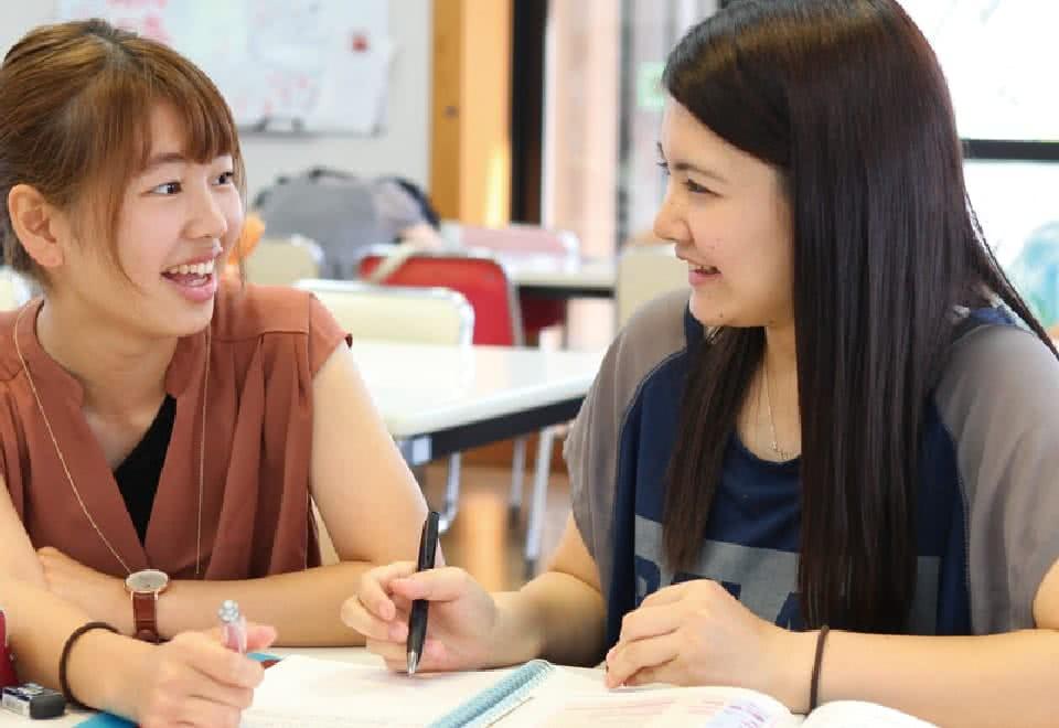 写真:笑顔でノートを広げている二人の女子生徒