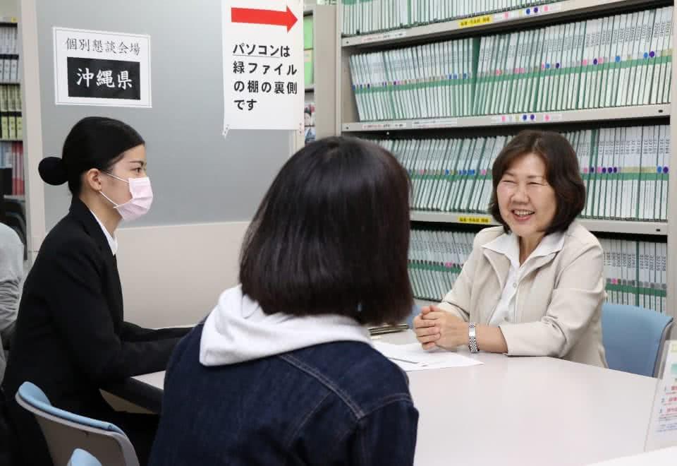 写真:面談している学生と笑顔で対応する現地スタッフ
