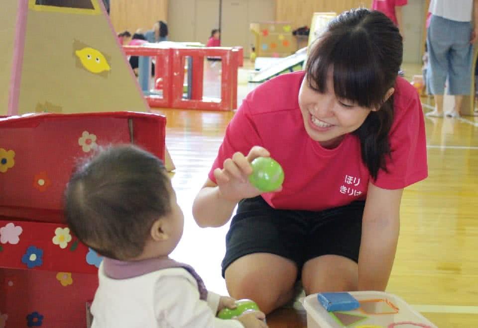 写真:みまさか子育てカレッジ。女性が赤ちゃんにボールを見せて遊んでいる様子