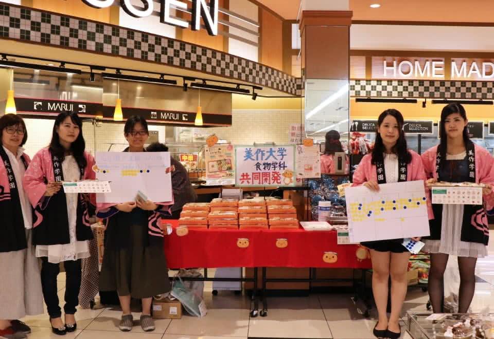 写真:マルイノースランド店にて実施した共同開発弁当販売キャンペーンでハッピを着て活動する人見研究室の学生たちと人見准教授