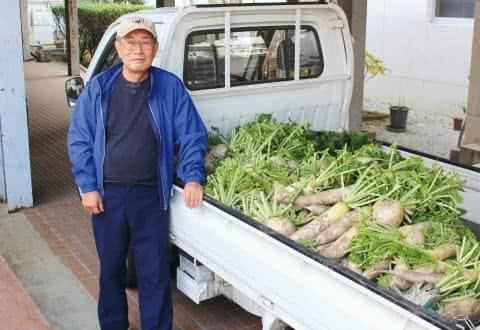 写真:軽トラックに積まれたたくさんの大根とその前に立つ美作学園 藤原理事長