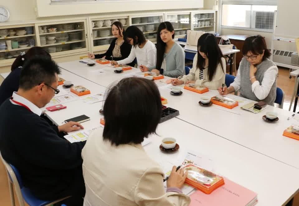 写真:マルイとの弁当開発会議で試作品を試食しながら議論する人見研究室の学生たち・人見准教授とマルイ社員