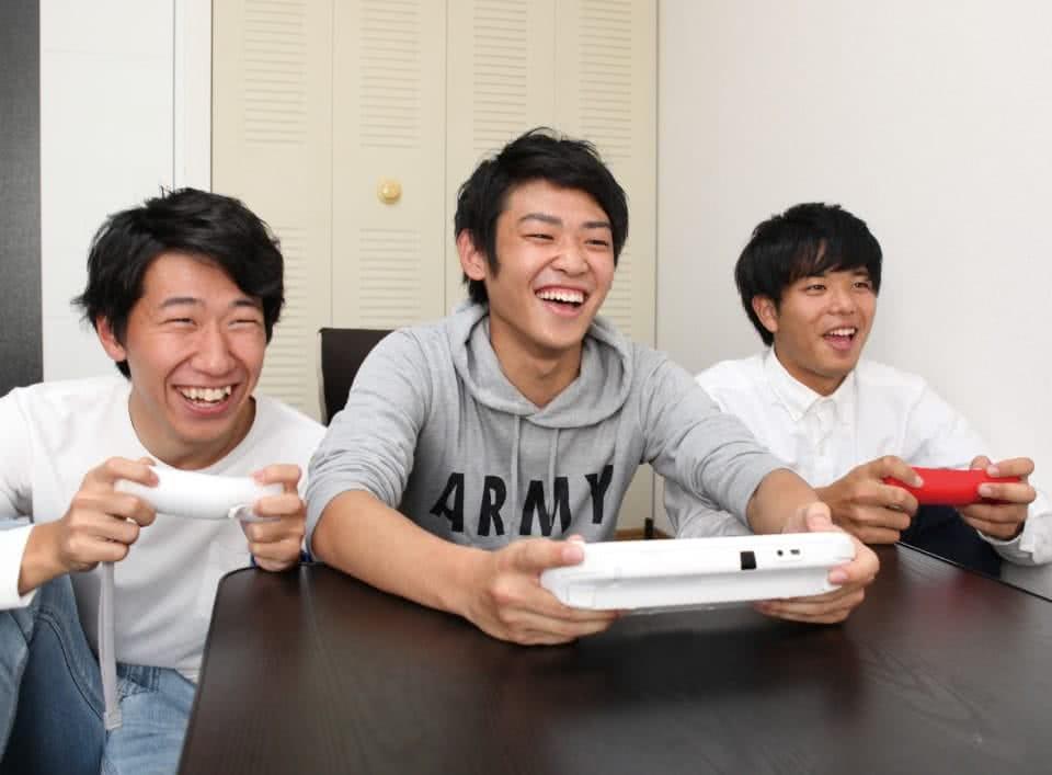 写真:アパートで友達二人とゲームを楽しむBさん