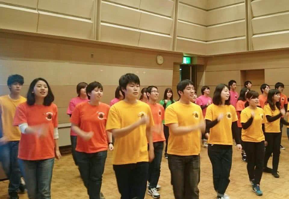 写真:ユニフォームを着てオープニングを歌う学生たち