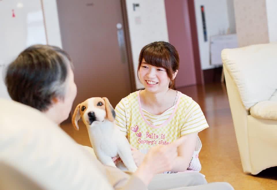 写真:女性が犬と一緒に患者さんにむかって笑顔で接している様子