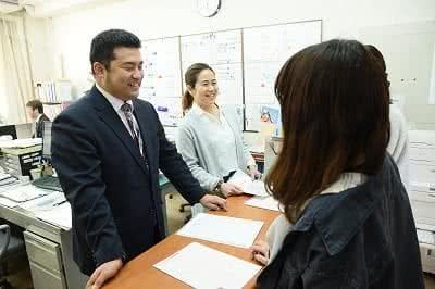 写真:就職支援室で指導にあたる二人のスタッフと指導を受ける女子学生