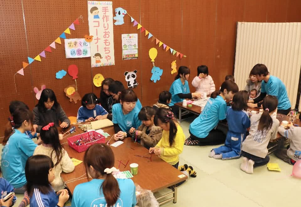 写真:地域のイベントで手作りおもちゃコーナーを開設する児童文化研究部と、そこで学生と一緒におもちゃを作る子どもたち