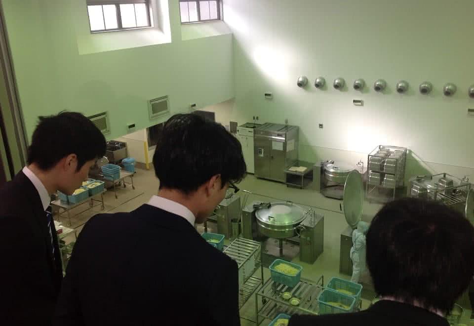 写真:給食センター見学。給食センターで給食が作られているのを見学している様子