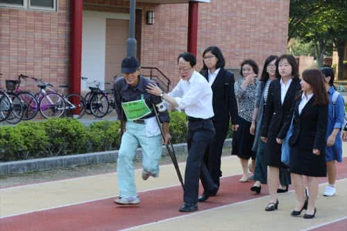 写真:要介助者と一緒に避難する教員と学生