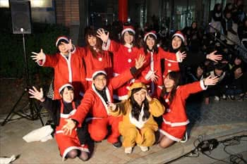 写真:サンタクロースとトナカイの衣装を身にまとった学生が手を広げてポースをする様子