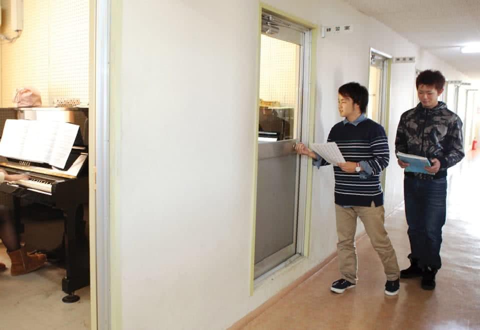 写真:男性が2名練習室にドアを開けて入ろうとしている
