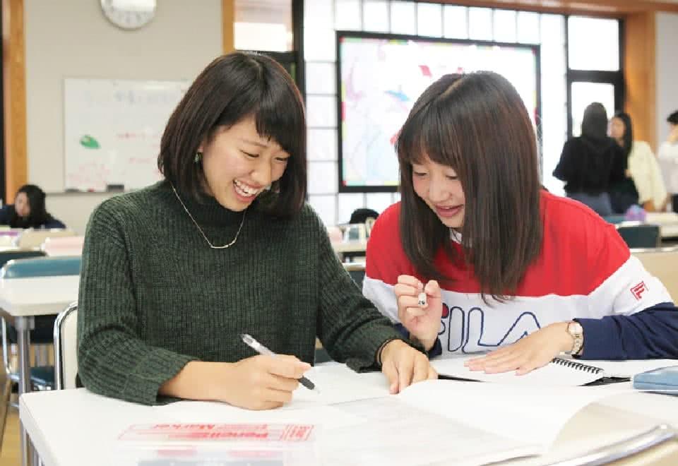 写真:友達とノートを開いているAさん