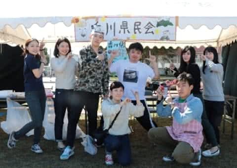 写真:香川県民会の看板を掲げた白梅祭の出店の前で、指を立てたポーズを取る香川県人会のメンバーたち
