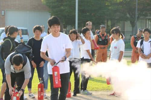 写真:消火器を使って火元を消化する学生