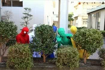 写真:ピクミンの格好をして茂みに隠れる4名の学生