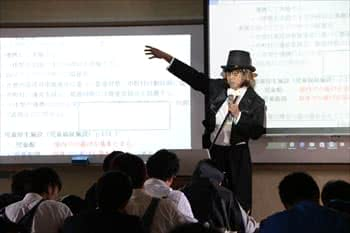 写真:チャップリンの格好をして教壇に立ちスライドを指さす有岡准教授