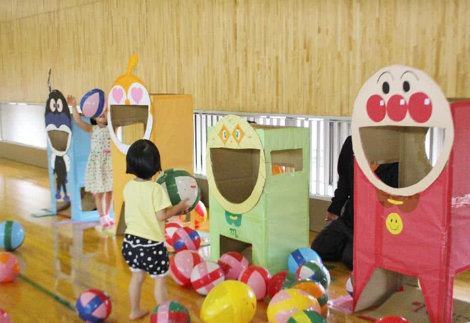 写真:アンパンマンのキャラクターの形をした手作りの遊具とそれで遊ぶ子ども