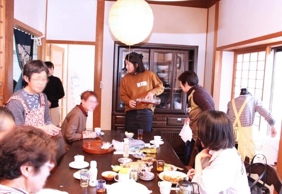 写真:食卓を囲んで会話するおあしすカフェ参加者と学生たち