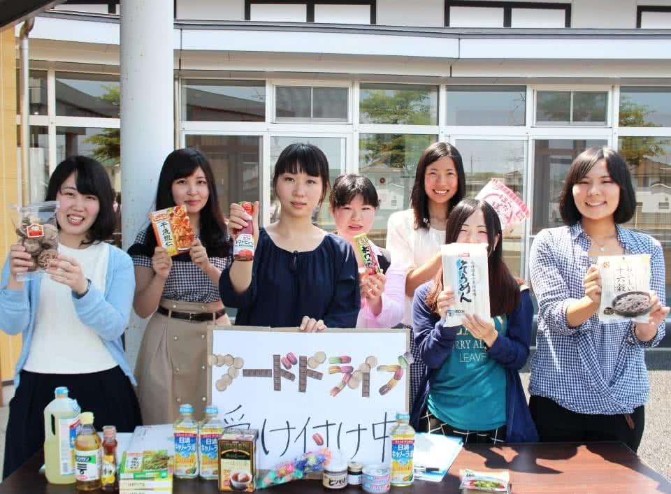 写真:「フードドライブ受付中」というパネルと様々な食品が置いてあるテーブルの後ろに、食品を手に持って並ぶ学生たち。