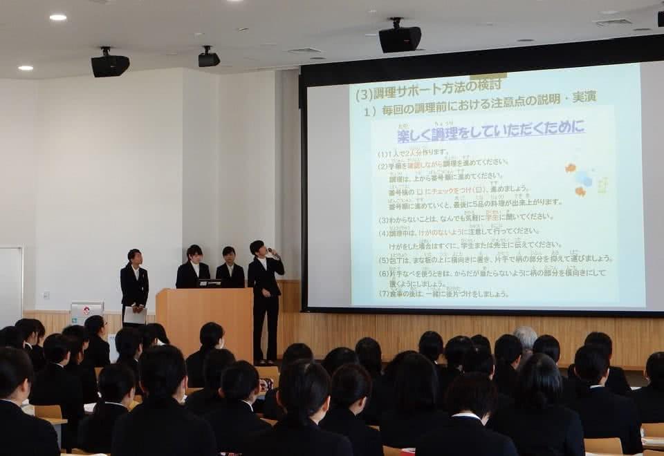 写真:大きなスクリーンに映し出されたものをグループで発表している様子