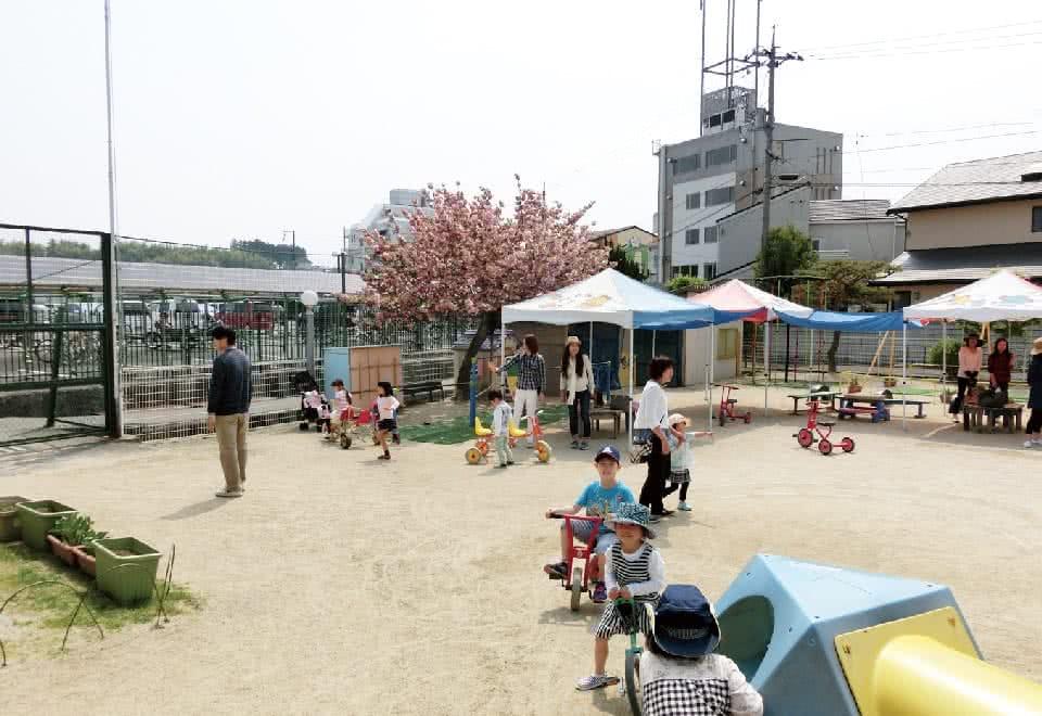 写真:附属幼稚園の園庭で遊ぶ子どもと保護者