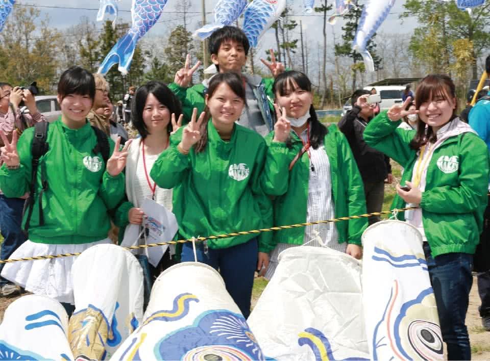 写真:揃いの緑色のジャケットを着て鯉のぼりを持つ学生スタッフたち