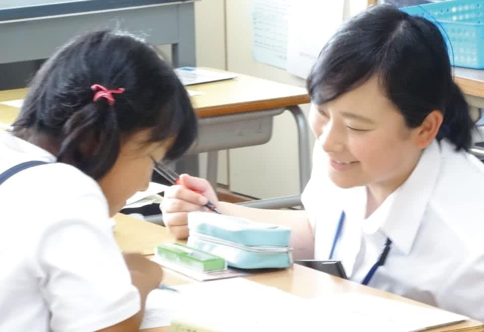 写真:授業支援として女子小学生に指導をする女子生徒