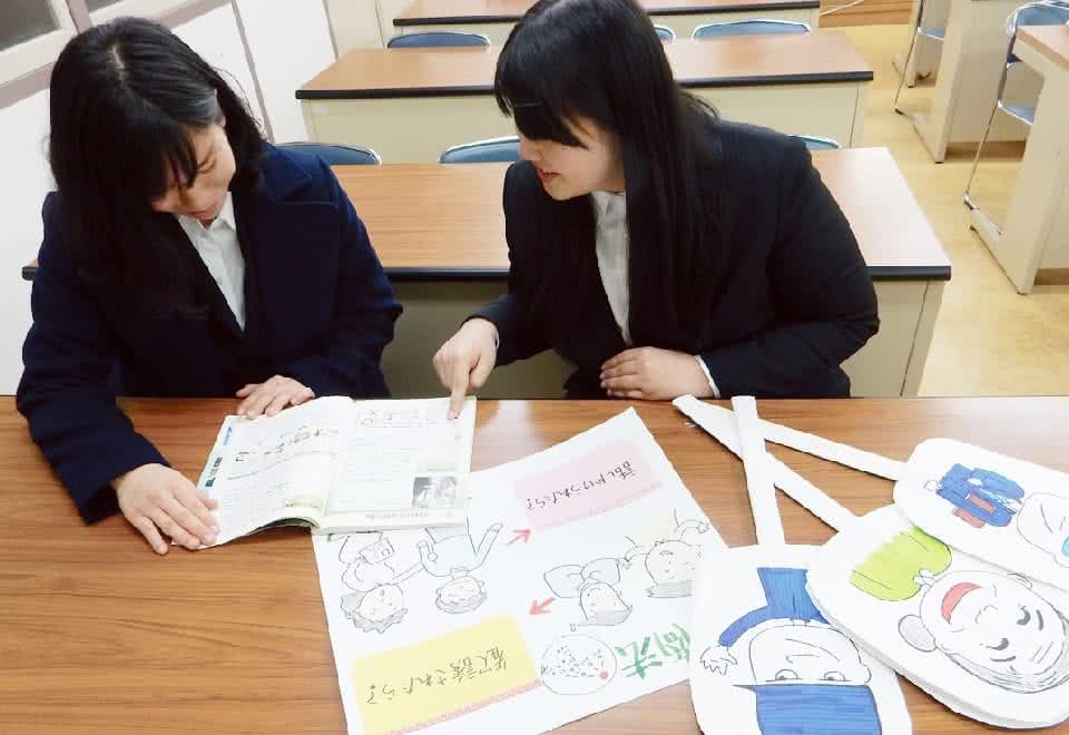 写真:女性が2人で机の上に手作りの教材を置いて体験学習をしている様子