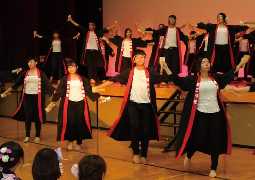 写真:屋内のステージで揃いの黒い衣装を着てよさこいを踊る高知県人会のメンバーたち