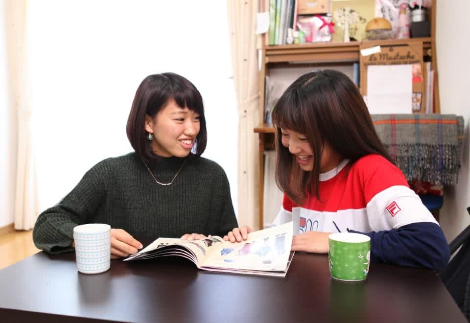 写真:アパートのローテーブルで雑誌を読む二人の女子学生