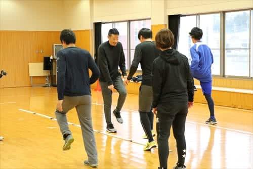 写真:体育館でリズムジャンプに挑戦する3名のスポーツ選手と、指導する津田准教授