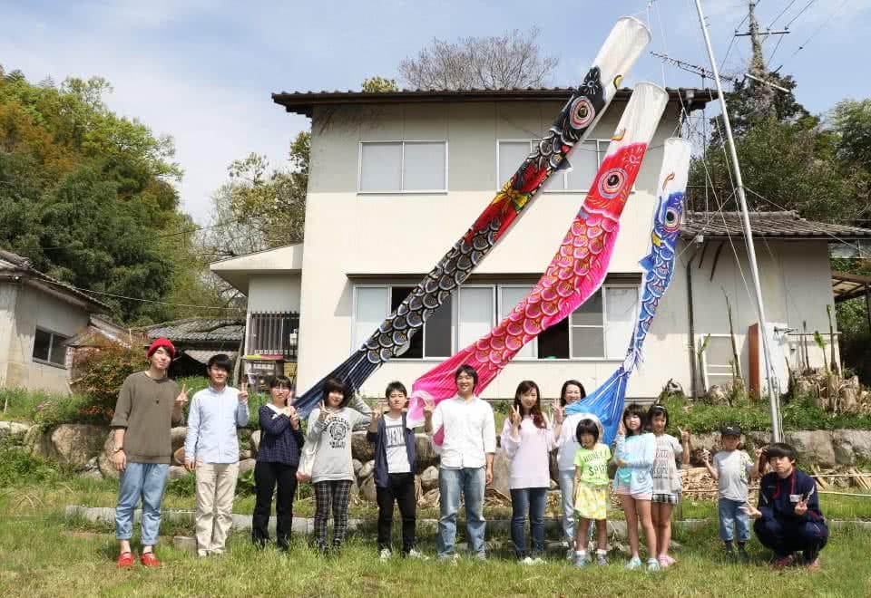 写真:じ・ば・子のおうちと鯉のぼりの前で記念撮影する子どもと高齢者、学生たち