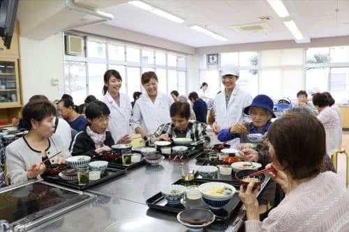 写真:ご飯を食べる地域の方と話す3名の学生