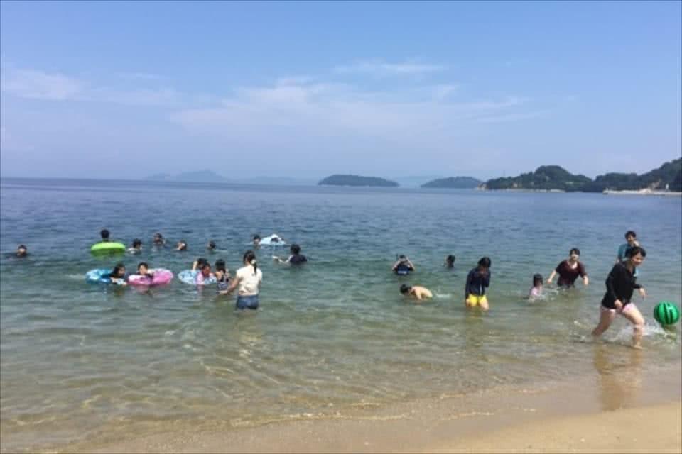 写真:海で、ボールを使って遊んだり、浮き輪を使って泳いだりする学生と笠岡諸島の子どもたち