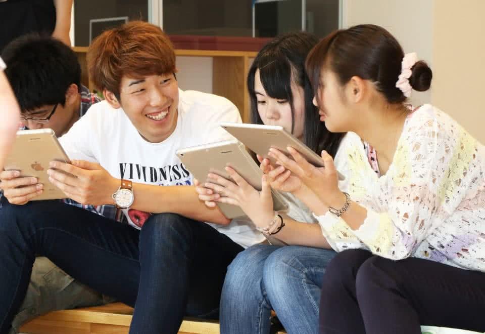写真:無線LANを使いタブレットを見る3人の学生たち