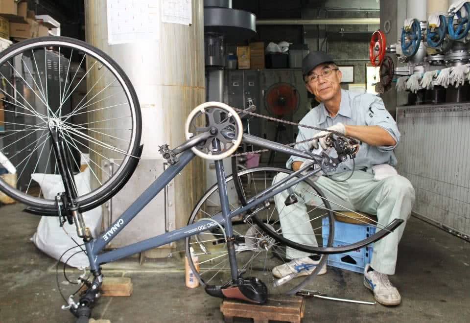 写真:自転車の修理をする男性の校務員さん