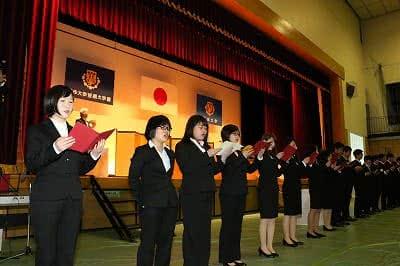 写真:ステージ前に整列して学歌を歌う在学生のコーラス隊